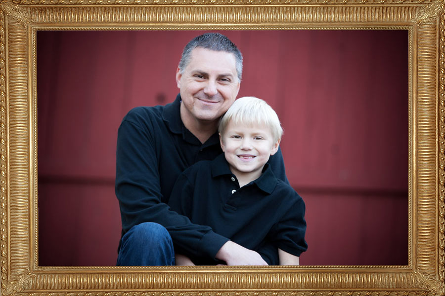 Family photos. Father and son portrait, in front of a red barn. Photographer: Hugh Anderson Photography.