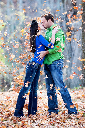 Engagement picture at Van Hoosen, Rochester Hills. The happy couple play with Fall leaves. Photographer: Hugh Anderson Photography.
